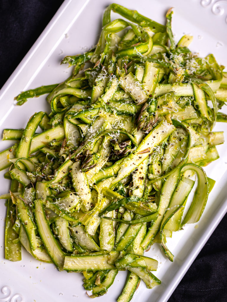 Shaved asparagus salad on a white platter.