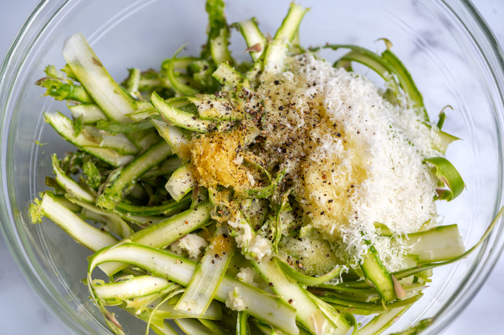 Shaved asparagus, grated Pecorino cheese, and lemon dressing in a bowl.