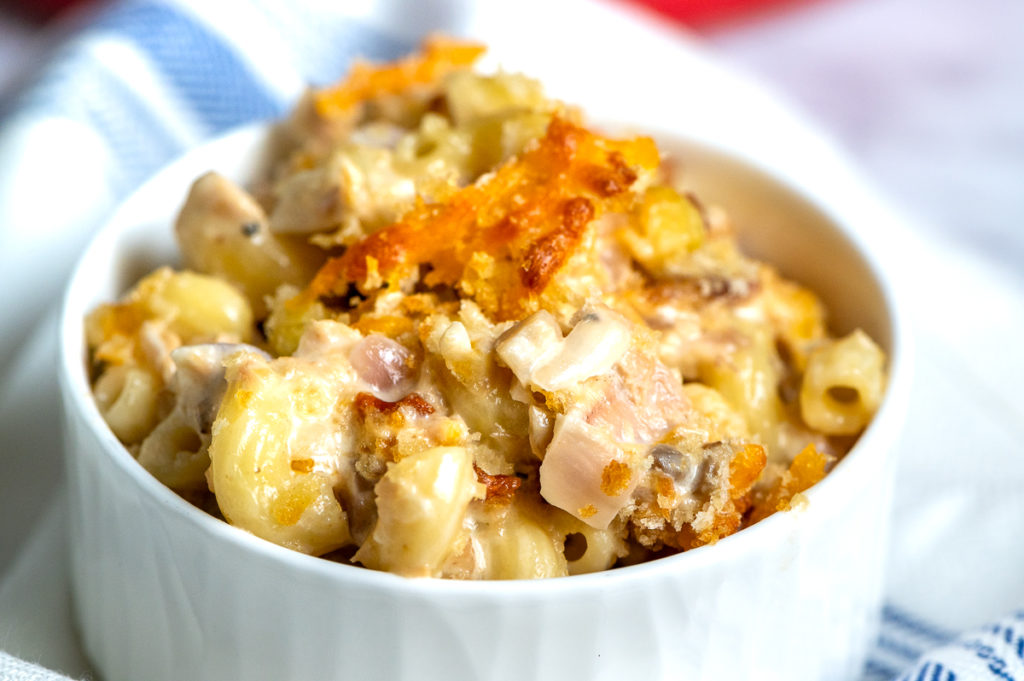 A small bowl filled with creamy pasta, tuna and a crunchy topping.