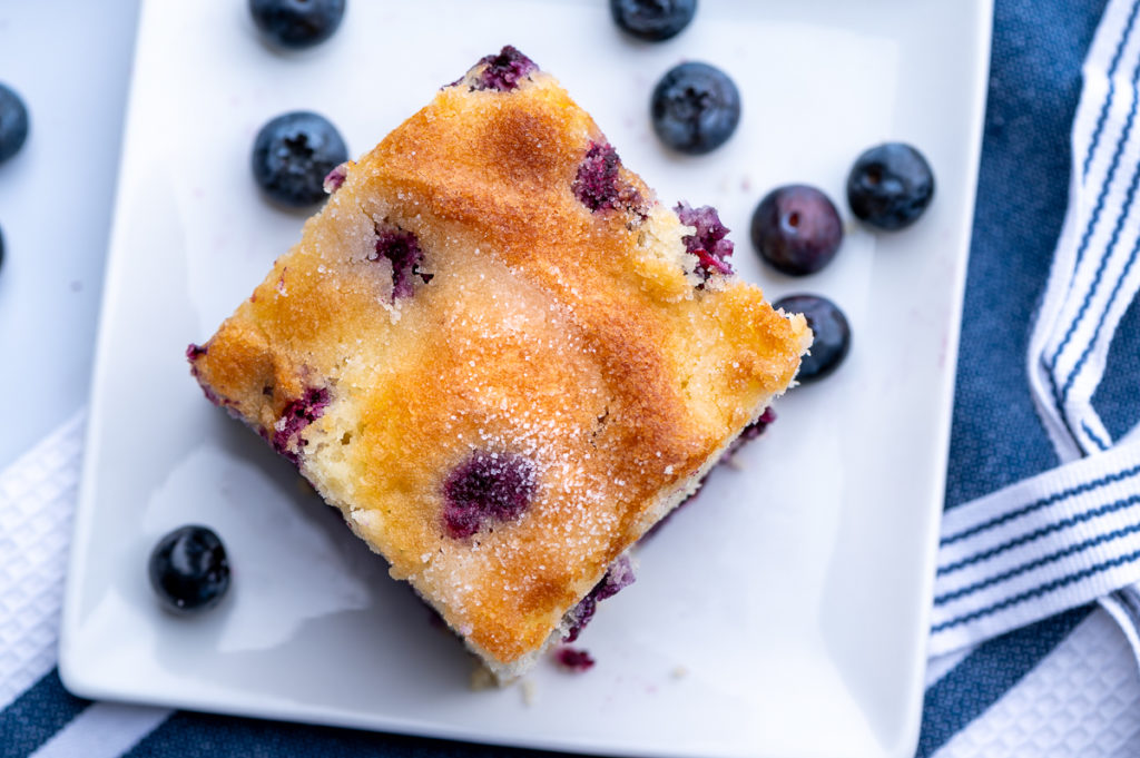 A slice of blueberry cake on a plate with loose blueberries.