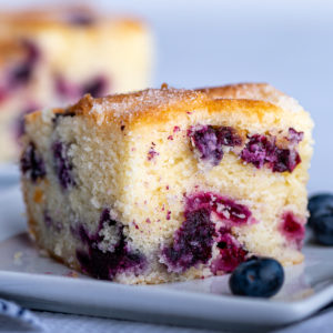 A slice of blueberry cake with a few blueberries surrounding it.
