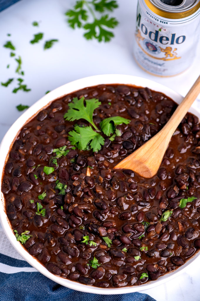 A white bowl of drunken black beans garnished with chopped cilantro.