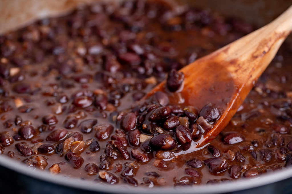 Black beans cooking in a skillet.