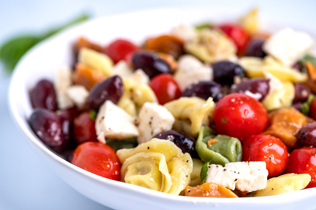 An angled view of a white bowl of pasta salad.