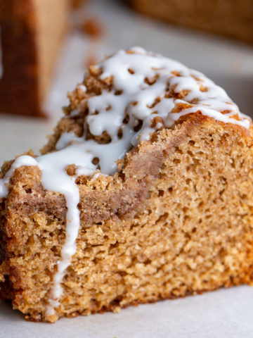 A slice of cinnamon coffee cake topped with glaze.