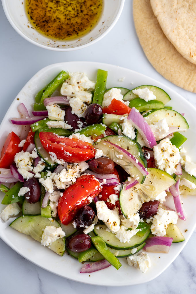 Greek salad on a white plate with dressing in a bowl and a slice of pita.