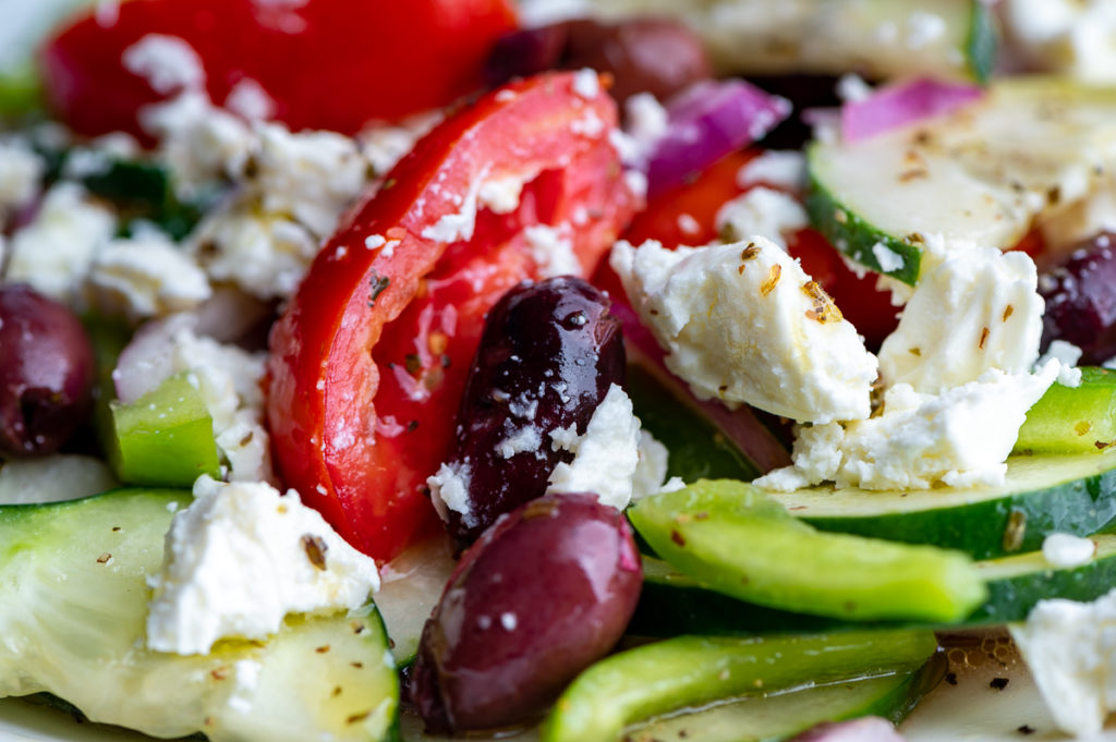 Closeup of tomatoes, olives, peppers and feta.