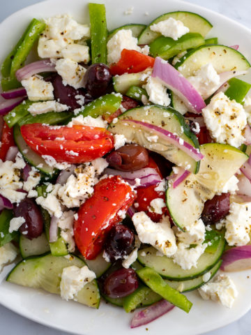 A white plate of Greek salad.