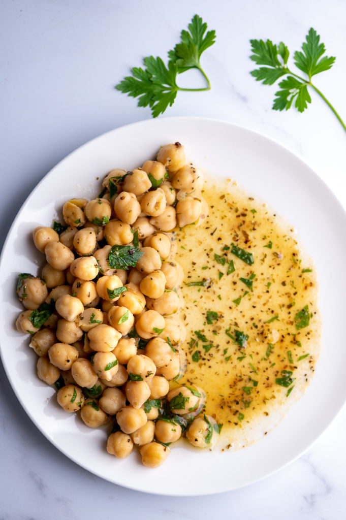 Marinated chickpeas on one side of a white plate with excess marinade covering other side.