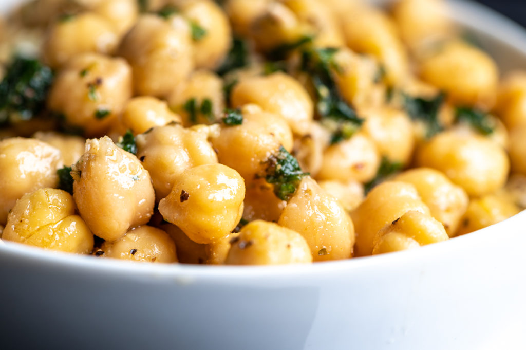 Chickpeas coated in dressing with chopped parsley.