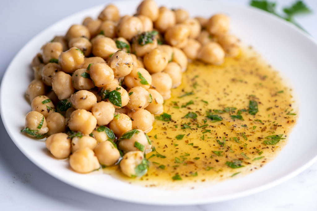 Marinated chickpeas on a white plate close up.