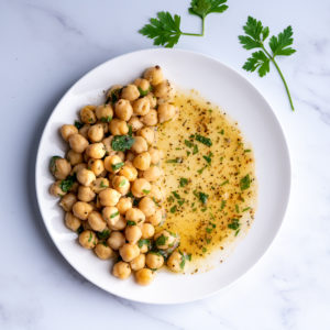 Chickpeas on one side of a white plate with a marinade on the other side.