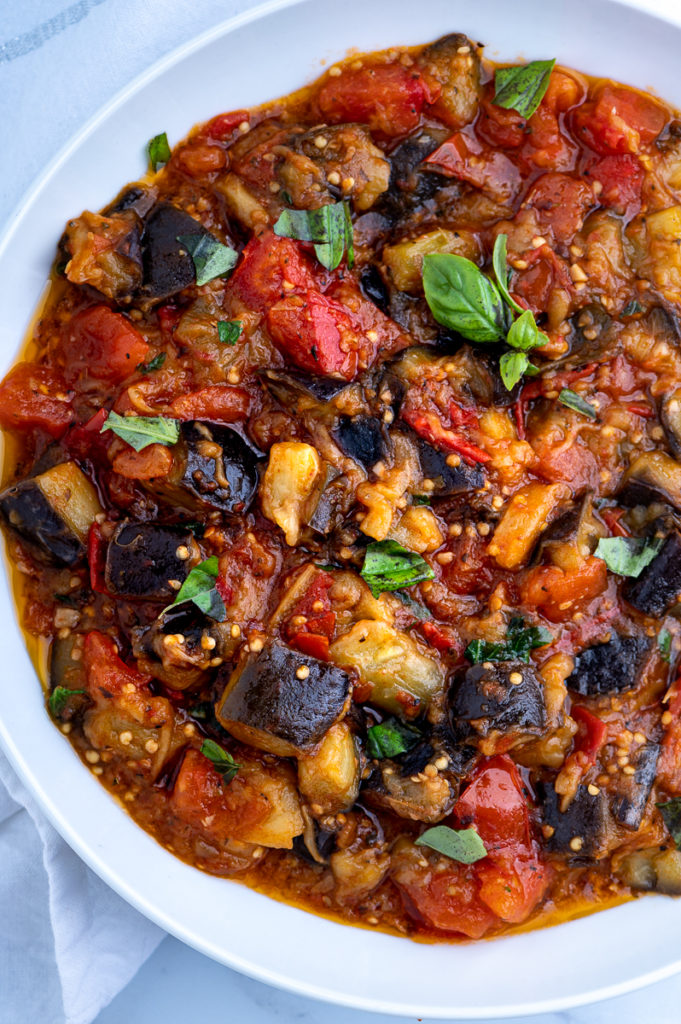 A white bowl of sautéed eggplant and tomatoes.