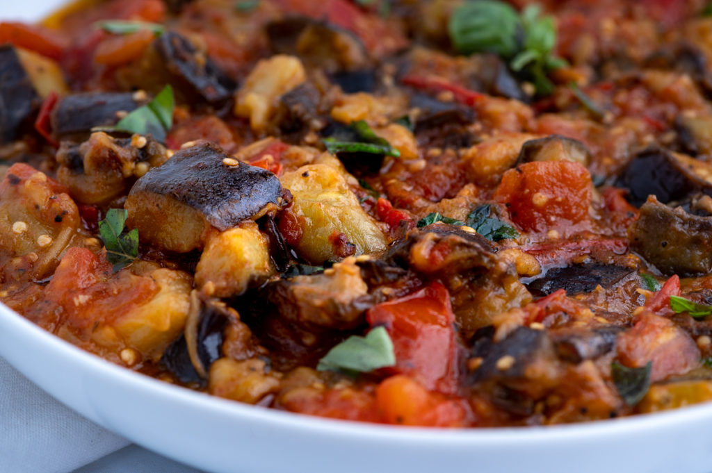 A bowl of cooked eggplant and tomatoes.