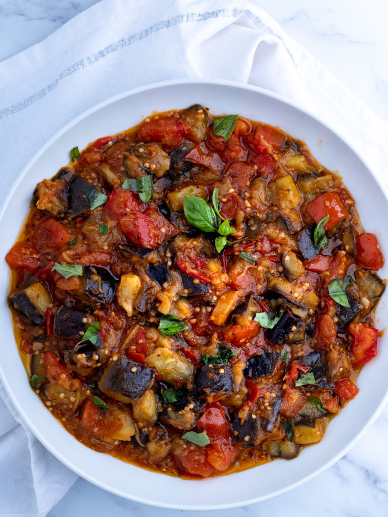 A white bowl of cooked eggplant and chopped tomatoes.