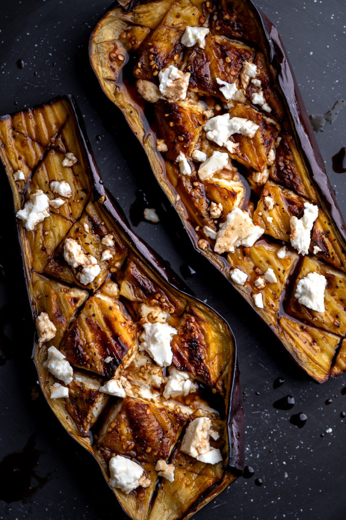 Two halved roasted eggplants with balsamic and feta on a black platter.