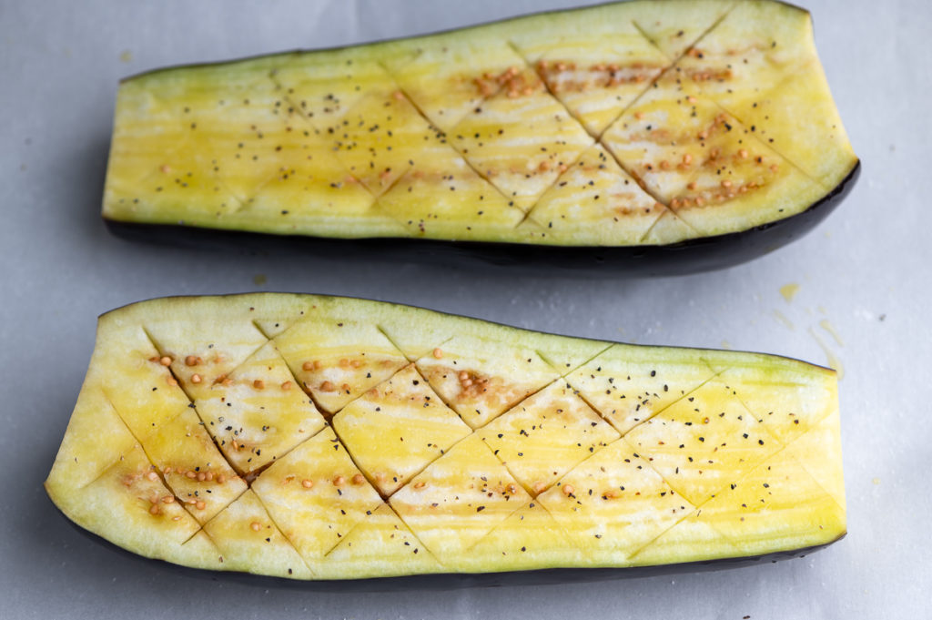 A halved eggplant scored and brushed with olive oil.