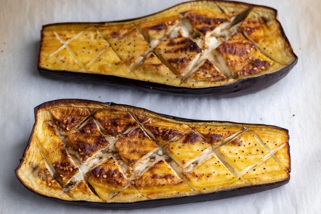 Scored and roasted eggplant halves.