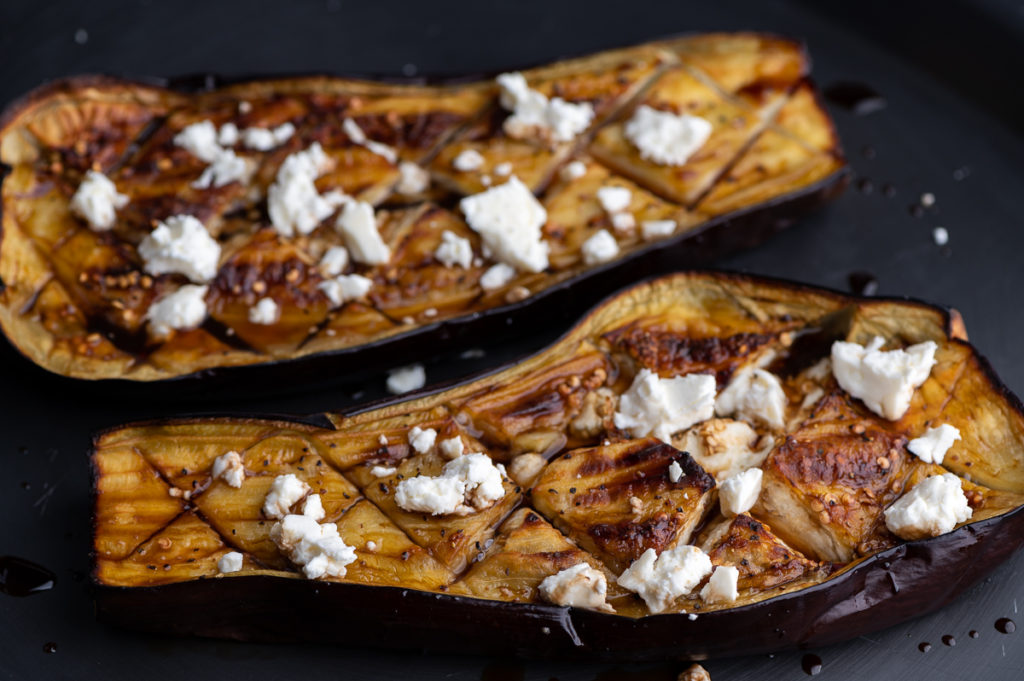 Two halved roasted eggplants with balsamic and feta.